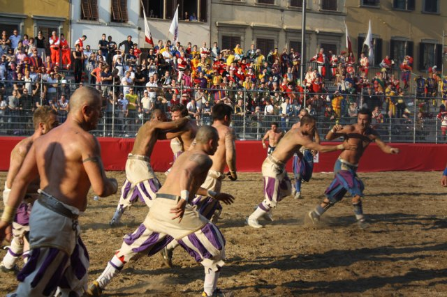 Calcio Storico in action, with parade participants looking on from the stands, via Around Tuscany